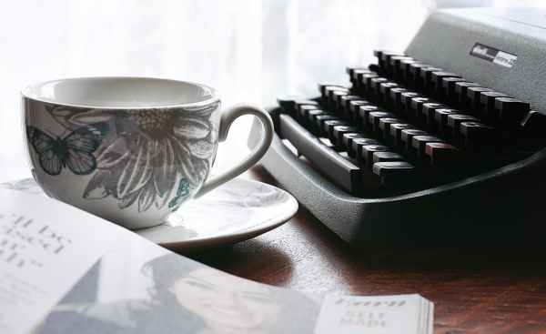 white and gray floral ceramic cup and saucer near black typewriter and book