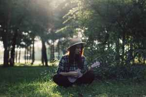woman sitting on grass playing ukulele